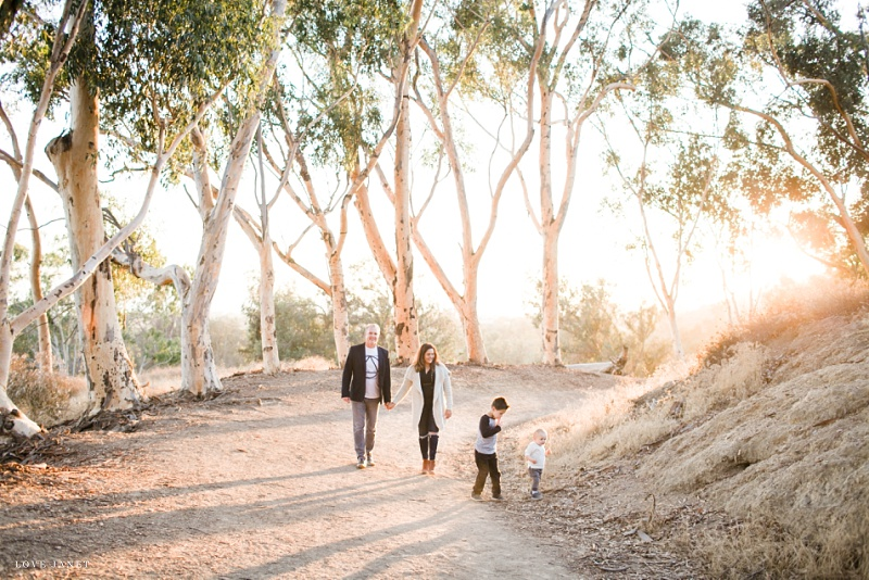 family of 4 during holiday mini sessions walking up a hill with the gorgeous golden light coming through the trees
